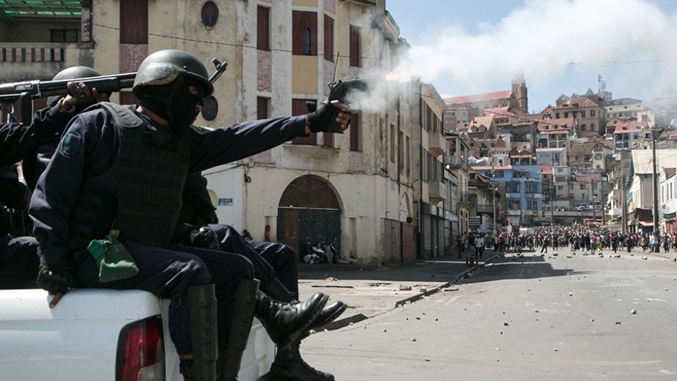 TOPSHOT - Police clash with protestors during a opposition demonstration against a draft electoral law adopted by Madagascar